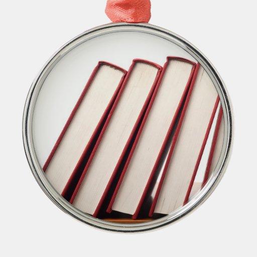 Fila de los libros que caen en orden adorno navideño redondo de metal