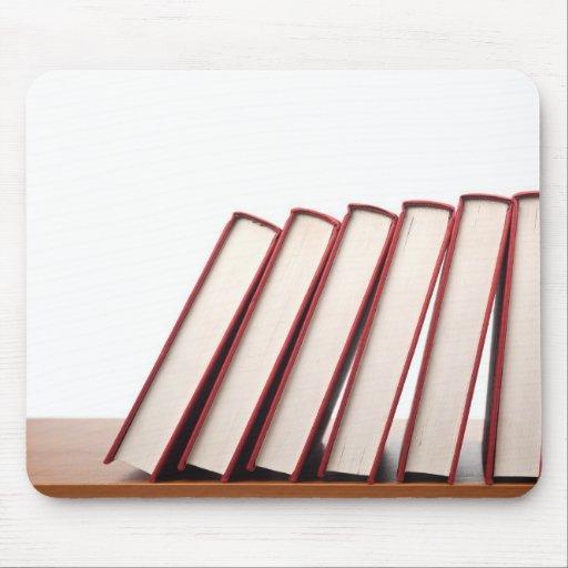 Fila de los libros que caen en orden tapete de raton