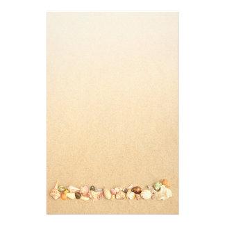 Fila de Seashells en la arena de la playa Papeleria