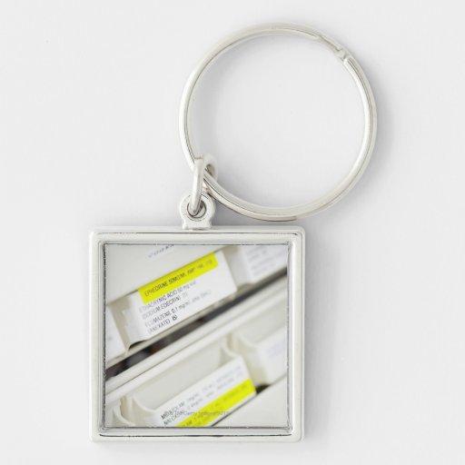 Filas de los cajones etiquetados de la medicina llavero cuadrado plateado