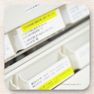 Filas de los cajones etiquetados de la medicina posavasos de bebidas