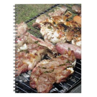 Filete y salchichas asados a la parilla en la libro de apuntes con espiral
