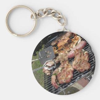 Filete y salchichas asados a la parilla en la llavero redondo tipo chapa