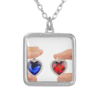 Fingers holding blue and red jewelry hearts