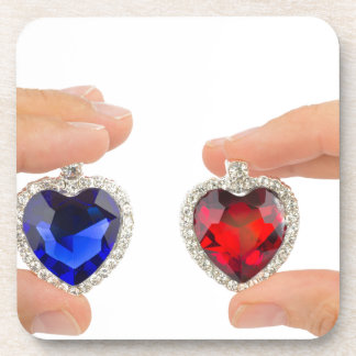 Fingers holding blue and red jewelry hearts coaster