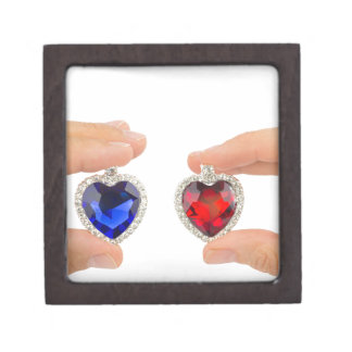 Fingers holding blue and red jewelry hearts gift box