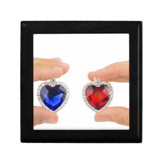 Fingers holding blue and red jewelry hearts jewelry box