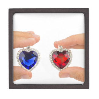 Fingers holding blue and red jewelry hearts keepsake box