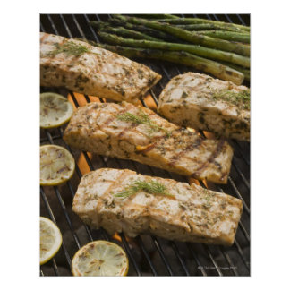Fish and asparagus cooking on grill poster