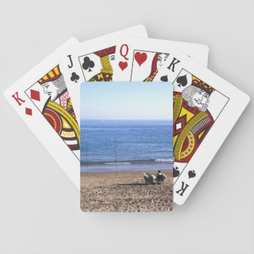 Fishermen in front of the sea playing cards