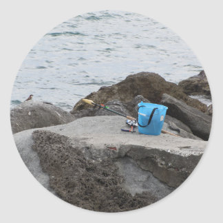 Fishing gear on the rock by the sea classic round sticker
