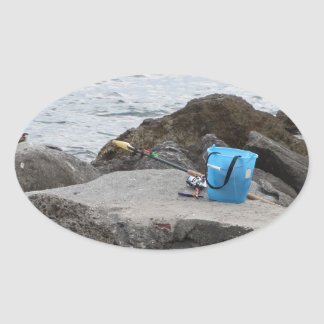 Fishing gear on the rock by the sea oval sticker