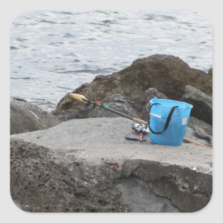 Fishing gear on the rock by the sea square sticker