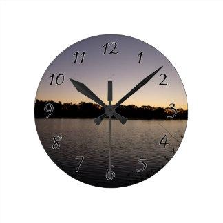 Fishing poles silhouette against the sun set clock