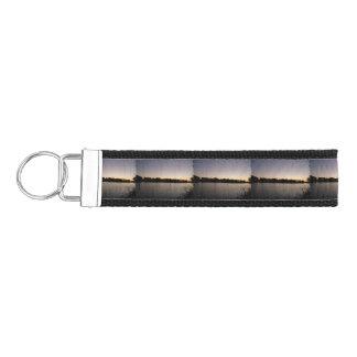 Fishing poles silhouette against the sun set wrist keychain