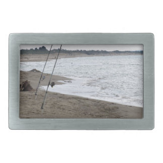 Fishing rods on a sandy beach at sunset belt buckle