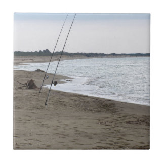 Fishing rods on a sandy beach at sunset ceramic tile