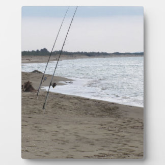 Fishing rods on a sandy beach at sunset photo plaque