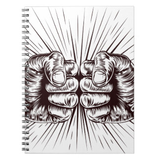 Fists punching spiral note books