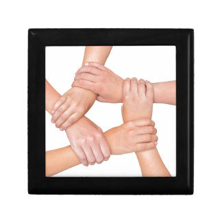 Five arms of children holding together on white gift box