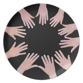 Five children hands joining in circle above black dinner plate