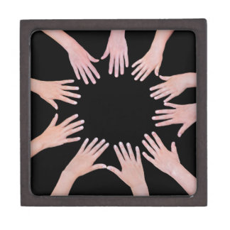 Five children hands joining in circle above black jewelry box