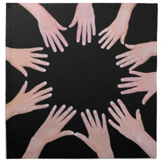 Five children hands joining in circle above black napkin