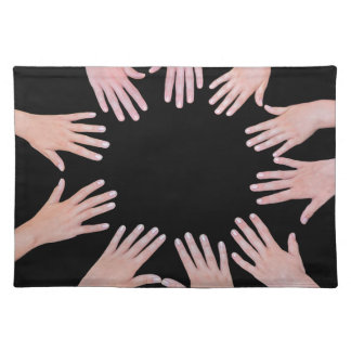 Five children hands joining in circle above black placemat