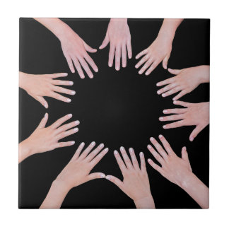 Five children hands joining in circle above black tile