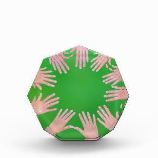 Five children hands joining in circle above green acrylic award