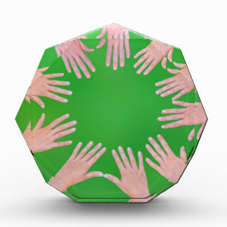 Five children hands joining in circle above green award