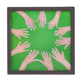 Five children hands joining in circle above green jewelry box