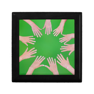 Five children hands joining in circle above green keepsake box