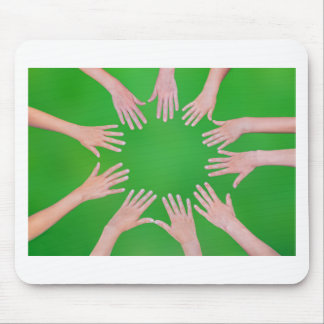 Five children hands joining in circle above green mouse pad