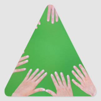 Five children hands joining in circle above green triangle sticker