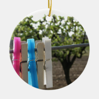 Five color clothespins hanging on rural background ceramic ornament