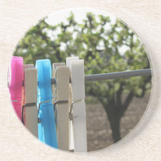 Five color clothespins hanging on rural background coaster