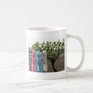 Five color clothespins hanging on rural background coffee mug