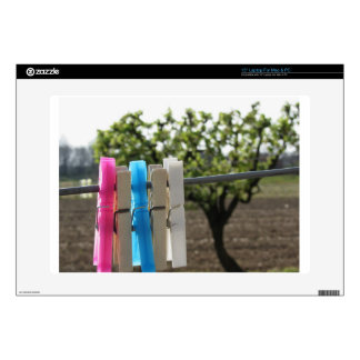 Five color clothespins hanging on rural background laptop decal