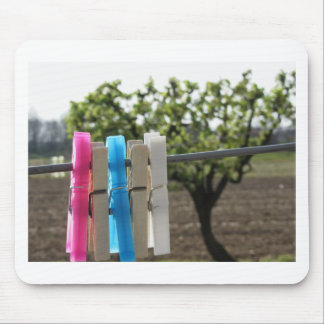 Five color clothespins hanging on rural background mouse pad