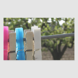 Five color clothespins hanging on rural background rectangular sticker