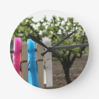 Five color clothespins hanging on rural background round clock