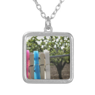 Five color clothespins hanging on rural background square pendant necklace