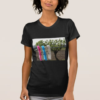 Five color clothespins hanging on rural background tee shirt