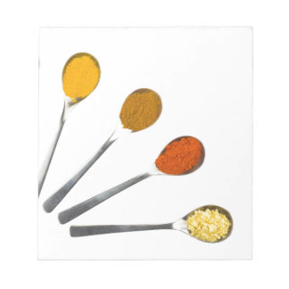 Five seasoning spices on metal spoons notepad