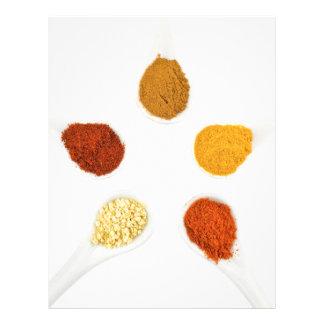 Five seasoning spices on porcelain spoons letterhead