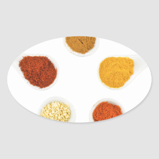 Five seasoning spices on porcelain spoons oval sticker