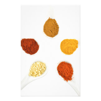 Five seasoning spices on porcelain spoons stationery