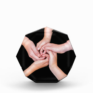 Five teenage arms with hands entangled on black acrylic award
