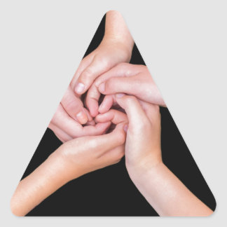 Five teenage arms with hands entangled on black triangle sticker